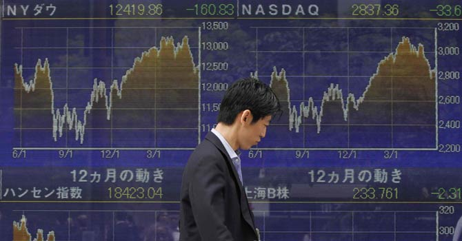 A trader walking past a screen at Tokyo Stock Exchange — File Photo