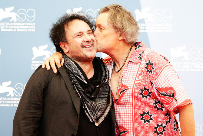 "US Director Jonathan Demme (R) kisses Italian singer Enzo Avitabile as they pose during a photocall for the movie ""Enzo Avitabile Music Life"" at the festival."