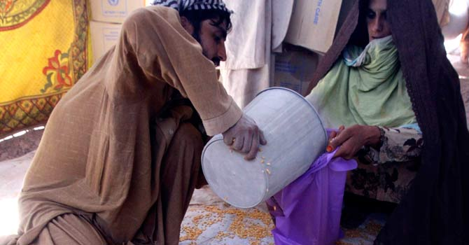 In this file photo from May, 2009, a woman who fled from fighting in the Swat Valley receives wheat  in the Jalozai camp on the  outskirts of Peshawar. – File photo by AP