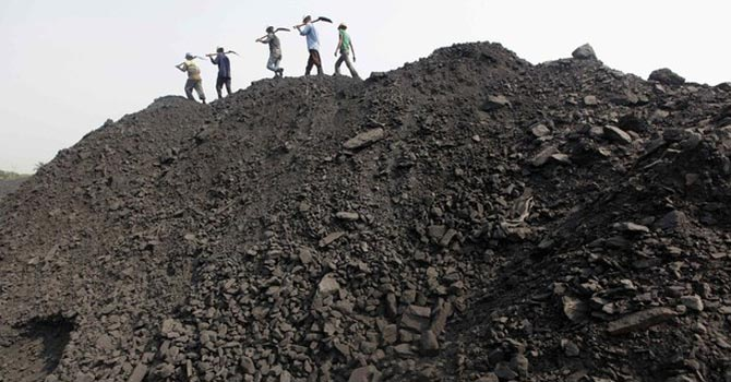 Workers walk on a heap of coal at a stockyard of an underground coal mine. — Reuters Photo