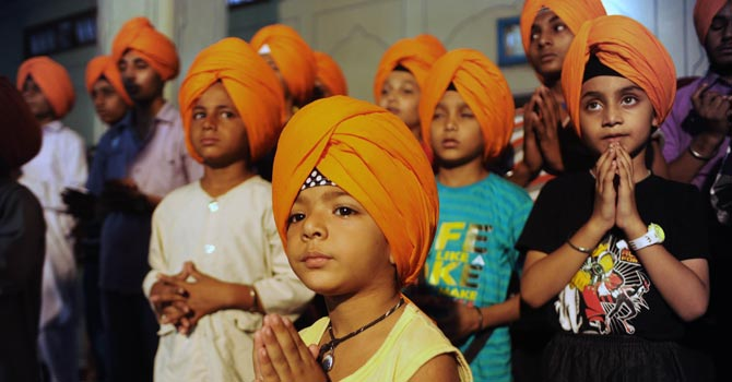 "Young Indian Sikh members praying after a turban-tying ceremony known as ""dastar bandi"", traditionally held to mark the coming of age of male Sikhs, at a temple in Amritsar.—AFP Photo"