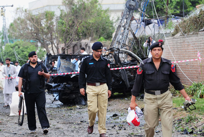 Pakistani policemen collect evidence at a bomb blast site in Peshawar on September 3, 2012.