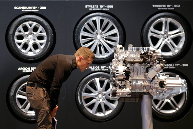 A visitor looks at an engine on media day at the Paris Mondial de l'Automobile. – Photo by Reuters
