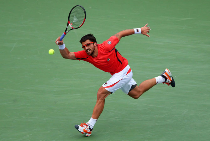 Janko Tipsarevic of Serbia returns a shot against David Ferrer of Spain during their men's singles quarterfinal match on Day Eleven of the 2012 US.