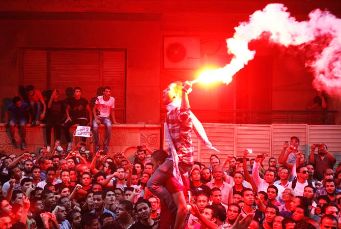 People shout slogans and light flares in front of the U.S. embassy. ? Photo by Reuters