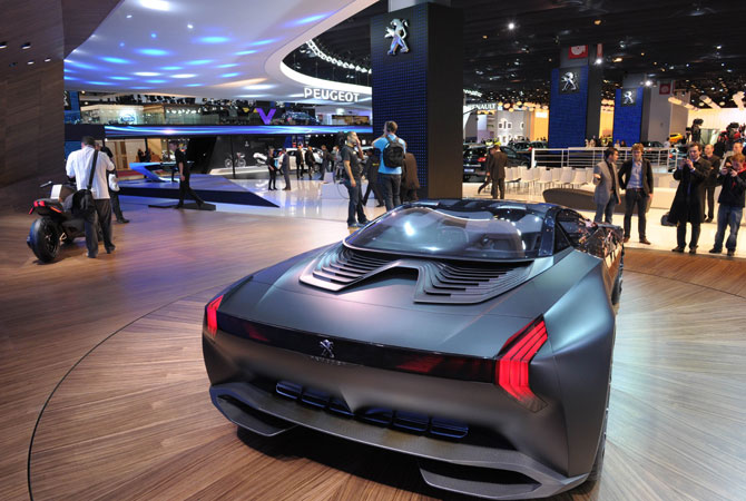 Visitors look at a Peugeot Concept car Onyx displayed on the French car maker stand during the press days ahead of the opening of the Paris Motor Show on September 27, 2012 at the Porte de Versaille exhibition center in Paris. – Photo by AFP