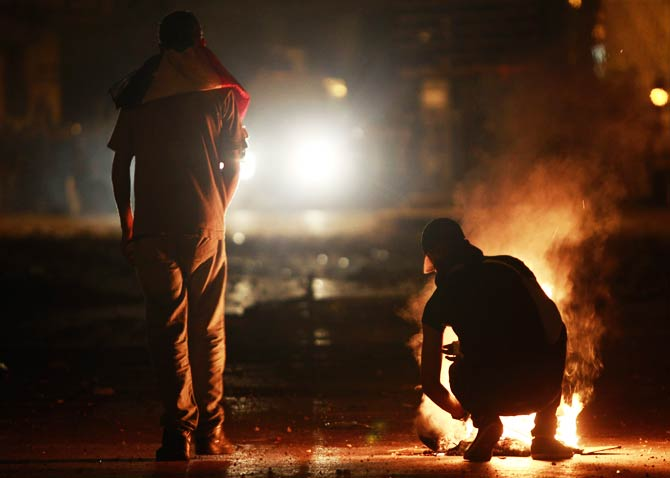 A protester starts a fire during clashes with riot policemen along a road that leads to the U.S embassy near Tahrir Square. ? Photo by Reuters