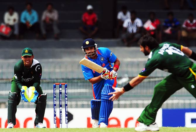 Rohit Sharma is watched by Pakistani wicketkeeper Kamran Akmal as he plays a shot. ? Photo by AFP