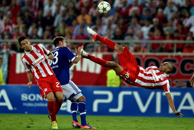 Olympiakos' Rafik Djebour (Right) shoots the ball during a group B Champions League football match against Schalke at the Karaiskaki stadium in Piraeus. ? Photo by AFP