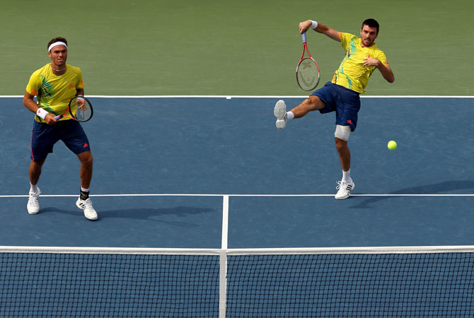Colin Fleming smashes the ball next to his partner Ross Hutchins of Great Britain during their men's doubles third round match against Ryan Harrison and Christian Harrison of the United States on Day Seven of the 2012 US Open.