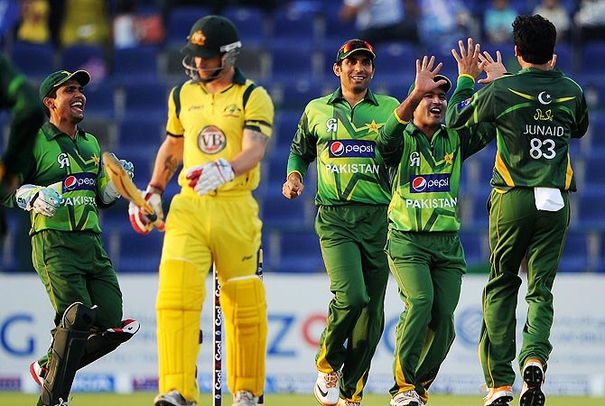 Junaid Khan (R) celebrates with teammates after taking the wicket of Matthew Wade. -Photo by AFP