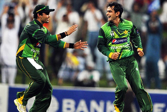 Mohammad Hafeez and Umar Akmal celebrate MIchael Clarke's dismissal. -Photo by AFP