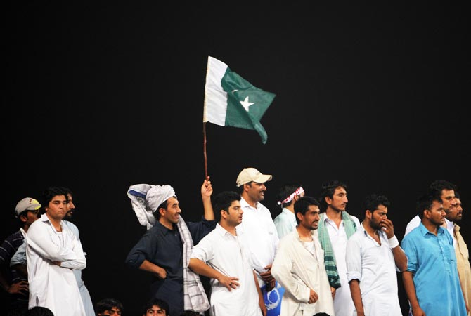 Pakistan cricket fans wave a flag and cheer on during the match. -Photo by AFP