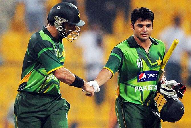 Misbah-ul Haq (L) shakes hand with teammate Azhar Ali after winning the match against Australia. -Photo by AFP