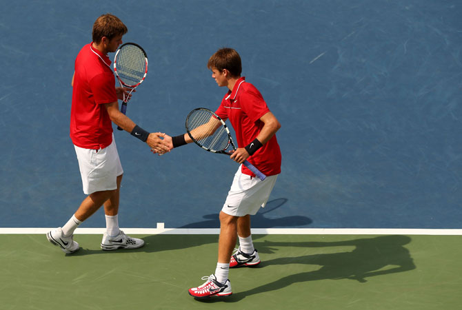Ryan (Left) and Christian Harrison of the United States tap hands during their men's doubles third round match against Colin Fleming and Ross Hutchins of Great Britain on Day Seven of the 2012 US Open.