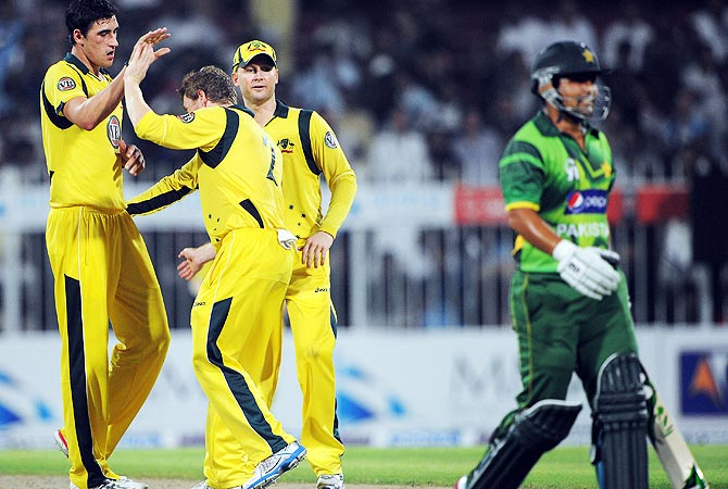 Australia players celebrate taking the wicket of Kamran Akmal. -Photo by AFP