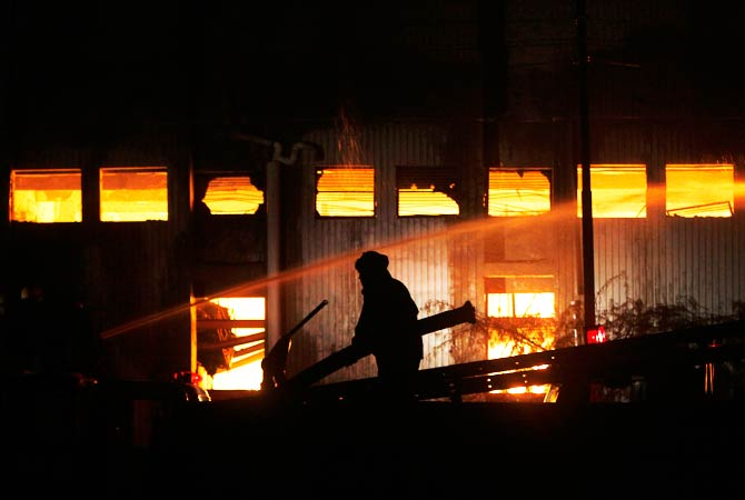 The silhouette of a firefighter can be seen in front of the blazing factory. ? Photo by AP