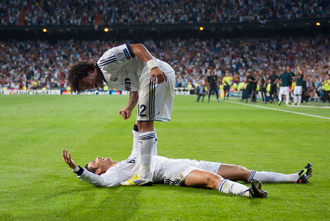 Real Madrid's Cristiano Ronaldo from Portugal, down, celebrates with Marcelo from Brazil after scoring a goal against Manchester City during a Champions League Group D match at the Santiago Bernabeu Stadium, in Madrid. ? Photo by AP