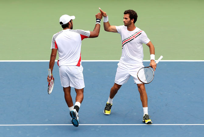 Aisam-Ul-Haq Qureshi of Pakistan and Jean-Julien Rojer of the Netherlands react against Christian Harrison and Ryan Harrison during their men's doubles quarterfinal match on Day Ten of the 2012 US.
