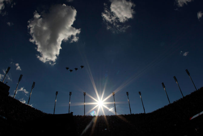 US Air Force F15e Strike Eagles fly over Arthur Ashe Stadium as members of the military unfurl the national flag before the start of the women's singles final match between Serena Williams of the United States and Victoria Azarenka of Belarus on Day Fourteen of the 2012 U.S. Open.