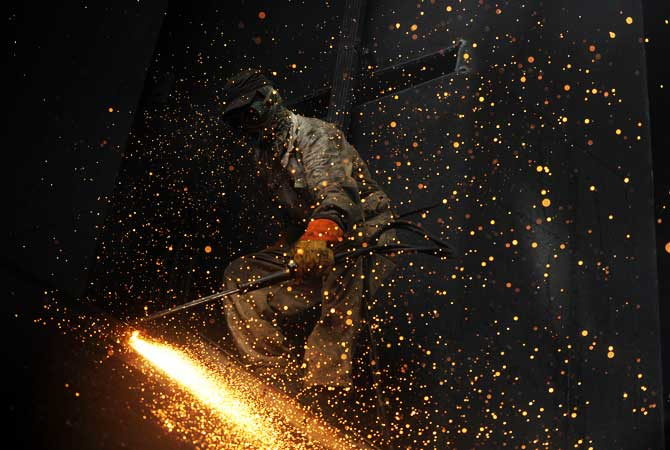 A worker uses a blow torch to cut through metal inside the hull of a vessel. ? Photo of AFP