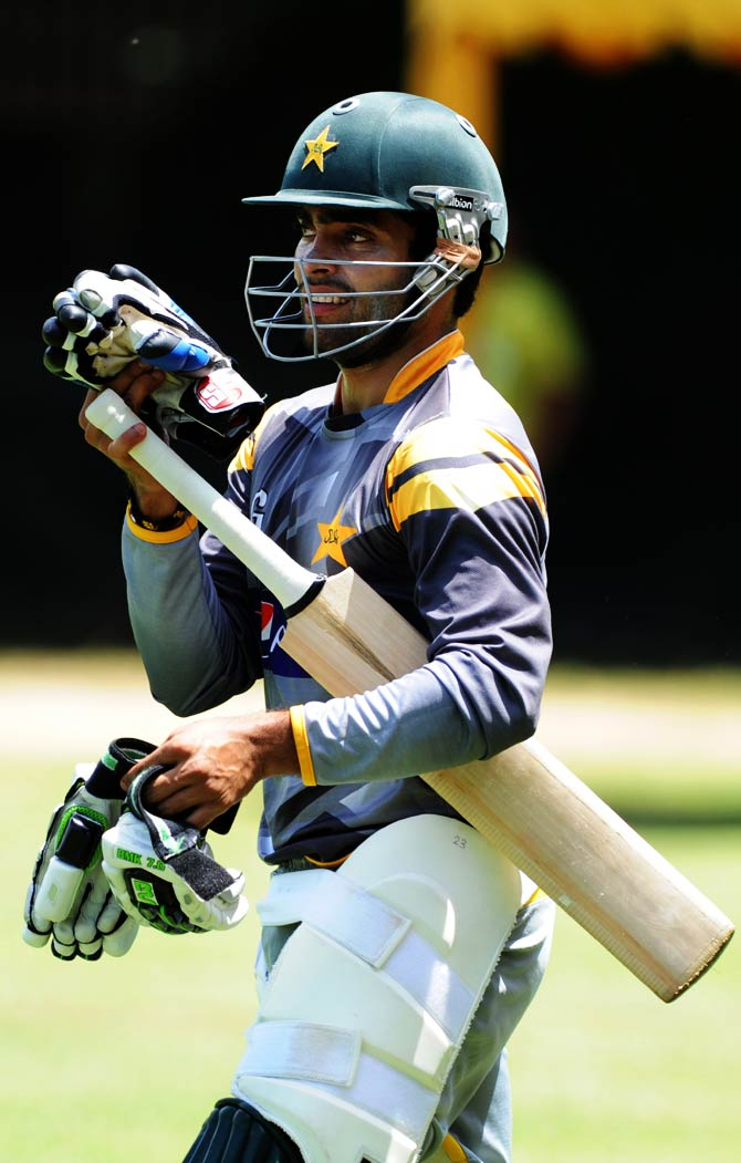 Pakistan cricketer Umar Akmal carries his equipment the practice session. ? Photo by AFP