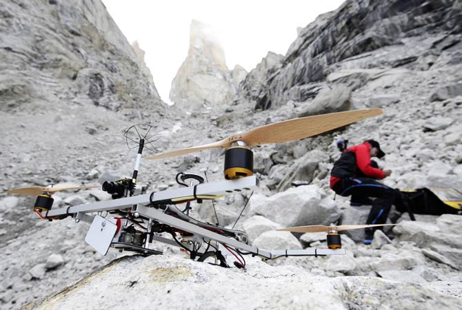 A team member gets ready to operate a helicopter over the Trango Summit.- Photo by AP