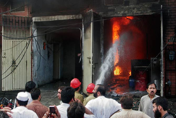Residents look on while firefighters try to extinguish a fire at a shoe factory in Lahore. ? Photo by Reuters