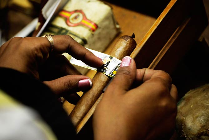 A woman fixes the ring on a cigar. ? Photo by Reuters