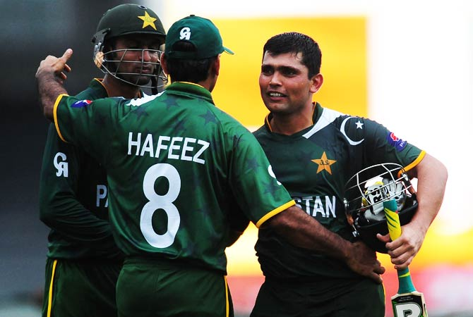 Kamran Akmal, and Shoaib Malik are congratulated by their team captain Mohammad Hafeez after their victory. ? Photo by AFP