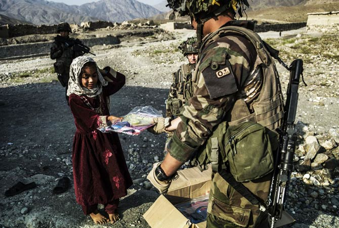 A French soldier gives an Afghan child a kite made by a French student association from Clermont Ferran. ? Photo by AFP