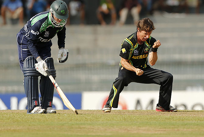 Brad Hogg, right, celebrates after taking the wicket of Ireland's batsman Gary Wilson, unseen. -Photo by AP