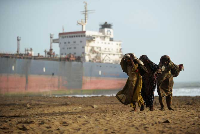 Workers carry sacks filled with scrap metal pieces they picked up on the shore. ? Photo by AFP