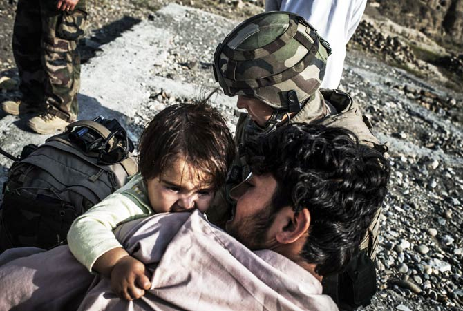 An Afghan child is treated by a French army medic. ? Photo by AFP
