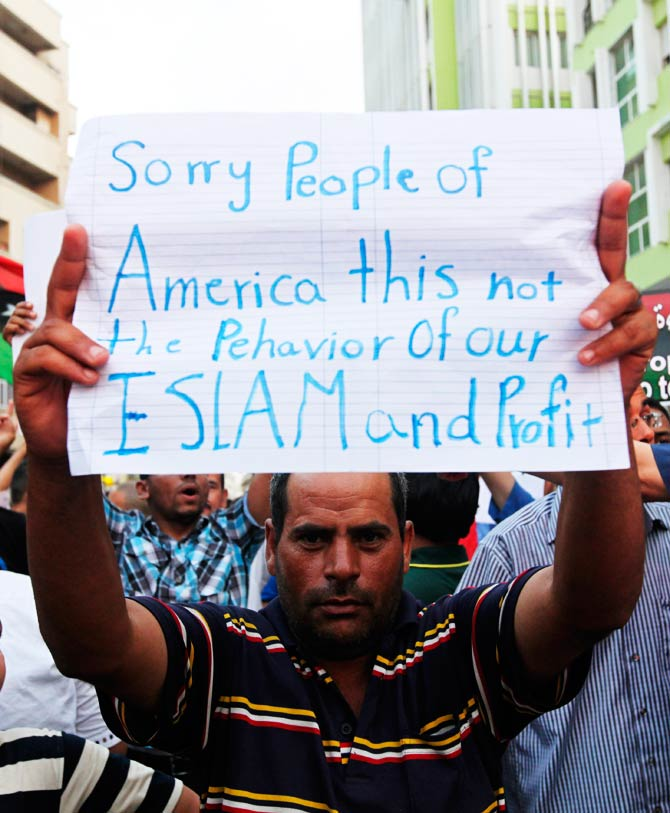 A Libyan demonstrator holds a message that reads 'sorry people of America, this is not the behavior of our Islam and Prophet.?