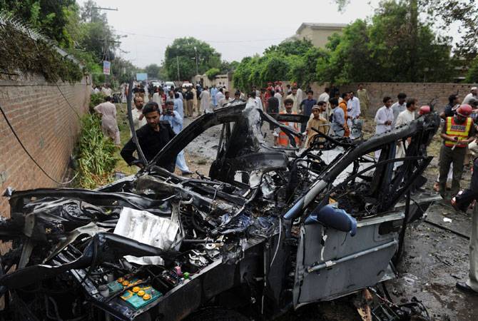 Pakistani rescuers and security personnel gather at a bomb blast site in Peshawar.