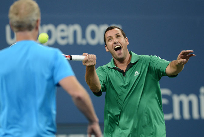Actor Adam sandler plays a shot while pairing with John McEnroe against Jim Courier and Kevin James during an exhibition match at the 2012 US Open.
