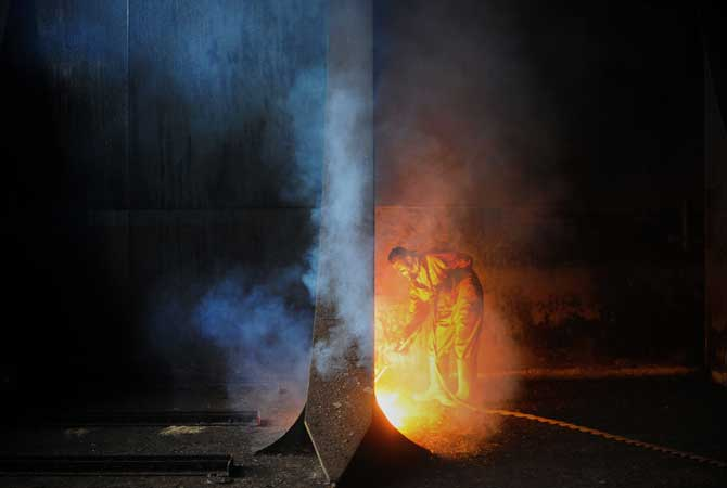 A worker is enveloped in the fumes coming off a separating wall he is cutting through with his a blow torch. ? Photo by AFP