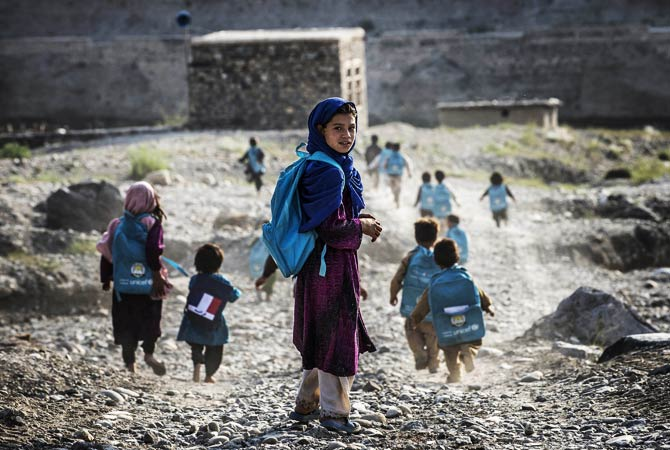Afghan children run to school in a village on the road to the French army base. ? Photo by AFP