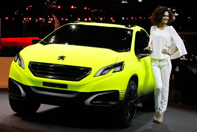 A hostess poses next to the new Peugeot 2008 Concept during media day at the Paris Auto Show, France. – Photo by AP