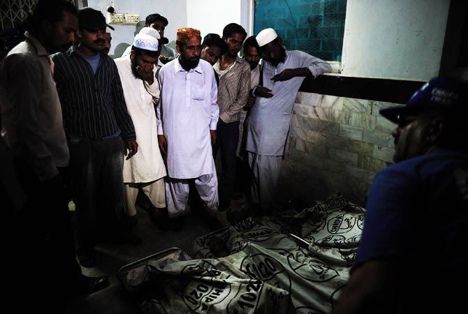 Pakistani people identify the dead bodies of workers after a garment factory was engulfed in a fire. ? Photo by AFP