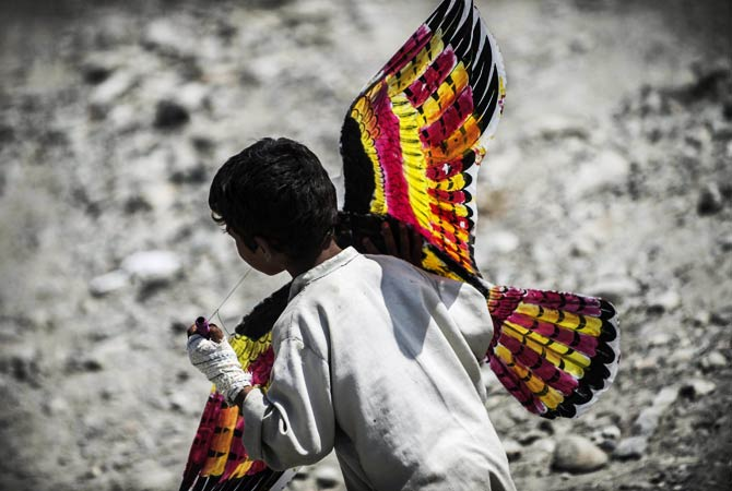 An Afghan child runs with a kite made by the French student association. ? Photo by AFP