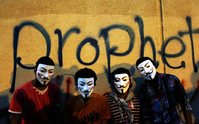 Egyptian protesters wearing Guy Fawkes masks pose in front of some graffiti. ? Photo by AP