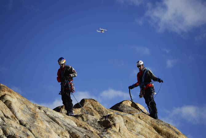 Mammut, Peter Ortner and David Lama walk on the Trango Summit in northern Pakistan's Karakoram mountain range while a remote-controlled helicopter flies over them. ? Photo by AP