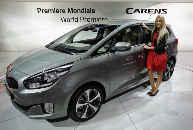 A hostess poses next to the Kia Carens, a compact MPV, during the Paris Auto Show, France. – Photo by AP