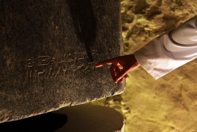 Mohammed Abd al-Sitar, 28, an archaeologist with the Egyptian Supreme Council of Antiquities points out a hieroglyph on a sarcophagus during the re-opening of the ?Serapeum?. ? Photo by AP