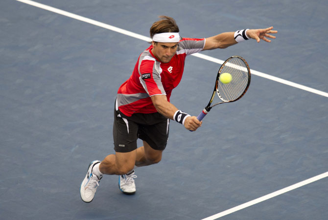 David Ferrer of Spain hits a return to Janko Tipsarevic of Serbia during their men's singles quarterfinal match at the 2012 US Open tennis tournament in New York.