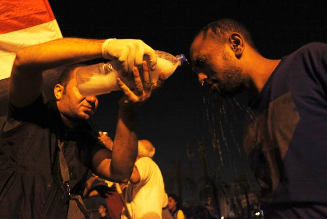 A protester has his eyes doused with milk after tear gas was fired during clashes with riot police. ? Photo by Reuters