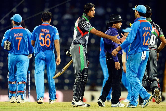 Afghanistan's Shapoor Zadran (C) shakes hands with India's players after the match. -Photo by Reuters