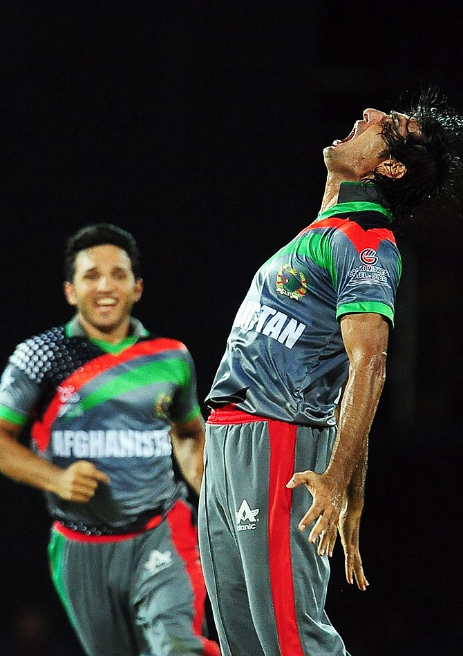 Afghanistan cricketer Shapoor Zadran (R) celebrates after he dismissed after he dismissed Indian cricketer Virender Sehwag. -Photo by AFP